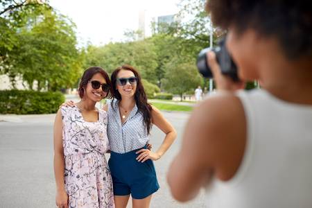 Female friendship, technology and people - woman with camera photographing her friends in summer park