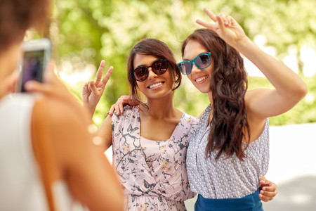 Female friendship, technology and people - woman with smartphone photographing her friends showing peace hand sign in summer park Imagens