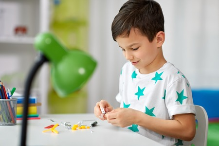 Childhood, hobby and leisure concept - little boy playing with building kit at home