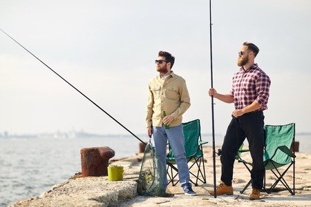 Leisure and people concept - happy friends with fishing rods and beer on pier at sea