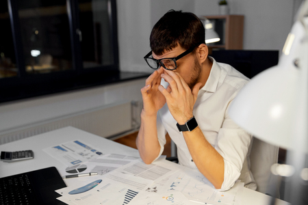 tired businessman working at night office Imagens