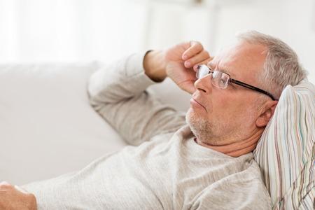 Alters-, Problem- und Menschenkonzept - Nahaufnahme eines älteren Mannes, der auf dem Sofa liegt und zu Hause denkt