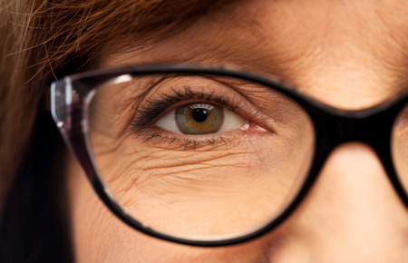 Beauty, vision and old people concept - close up of face of senior woman in glasses Imagens