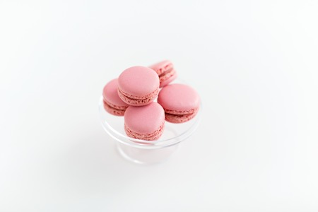 Sweets, pastry and food concept - Pink macaroons on glass confectionery stand over white background Stock Photo