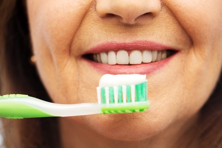 Dental care and hygiene people concept - close up of smiling senior woman with toothbrush brushing her teeth over white background