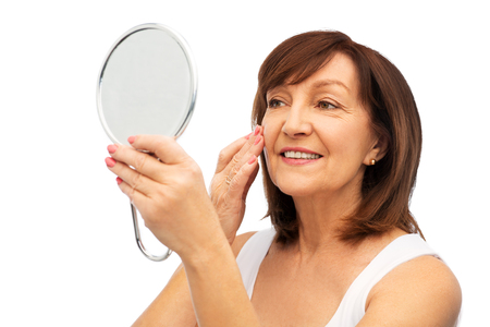 portrait of smiling senior woman with mirror Фото со стока