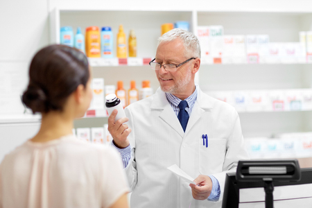 Medicine, pharmaceutics, healthcare and people concept - senior apothecary with drug and prescription and female customer at pharmacy