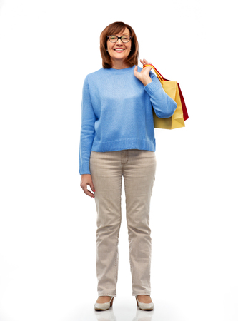 Sale and old people concept - smiling senior woman in glasses with shopping bags over white background Stock Photo