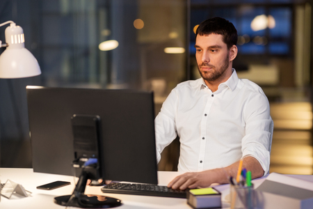 Business, overwork, deadline and people concept - businessman with computer working at night office