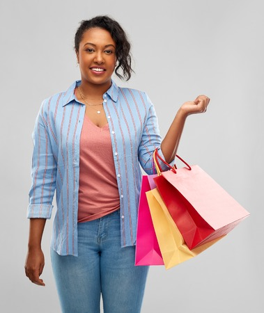 Sale and outlet concept - happy African American young woman with shopping bags over grey background Imagens