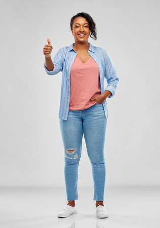 Gesture and people concept - smiling young African American woman showing thumbs up over grey background