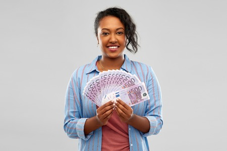 People, finances and wealth concept - happy African American young woman holding fan of euro money over grey background