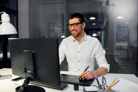 Business, graphic design and technology concept - designer or businessman in glasses with computer and pen tablet working at dark night office Imagens