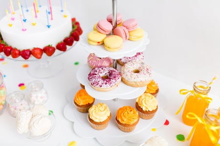 Party food and festive concept - close up of different sweets on stand and birthday cake