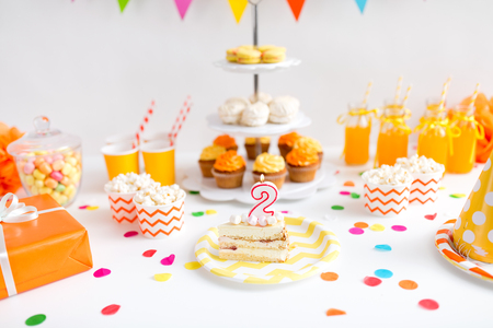 Anniversary, celebration and festive concept - piece of cake with candle in shape of number two on plate at birthday party