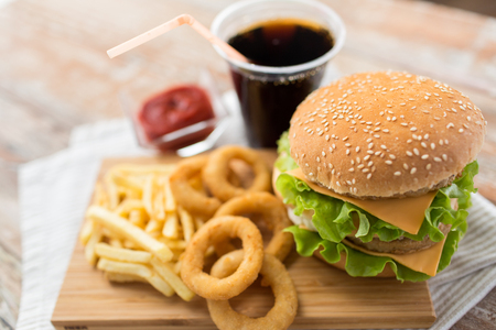 Fast food and unhealthy eating concept - close up of double hamburger or cheeseburger, deep-fried squid rings, french fries, cola drink and ketchup on wooden board Imagens