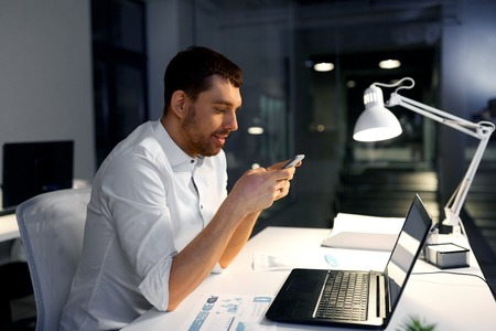 Business, deadline and technology concept - businessman with smartphone and computer working at night office