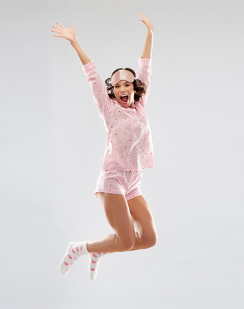 happy woman in pajama and eye mask jumping
