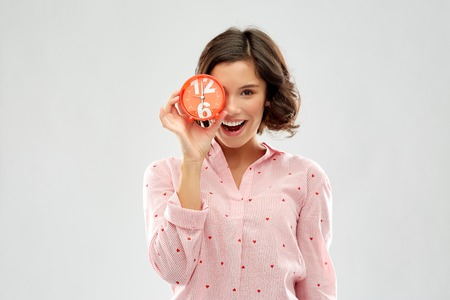 happy young woman in pajama with alarm clock