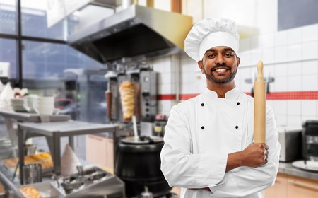 happy indian chef with rolling-pin at kebab shop Stock Photo