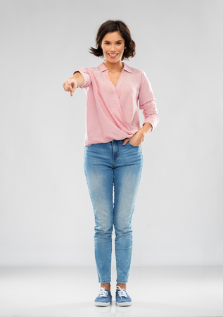 young woman in shirt and jeans pointing to you