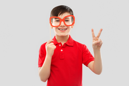 smiling boy with big paper glasses showing peace