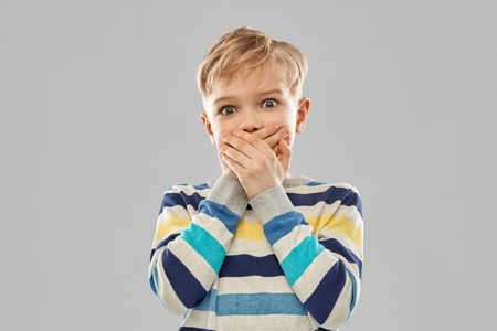 shocked little boy closing his mouth by hands Stock Photo - 120956636