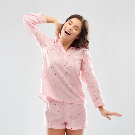 happy young woman in pajama stretching