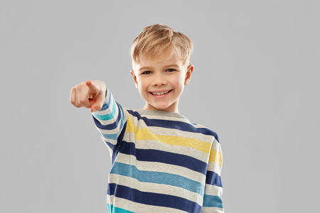 smiling boy in striped pullover pointing finger Stock Photo
