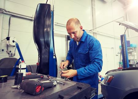 Concepto de servicio, reparación, mantenimiento y personas de automóviles - hombre mecánico de automóviles con llave y lámpara trabajando en el taller