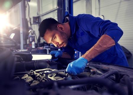 Concepto de servicio, reparación, mantenimiento y personas de automóviles - hombre mecánico de automóviles con lámpara trabajando en el taller