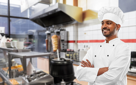 cooking, profession and people concept - happy male indian chef in toque over kebab shop kitchen background Stock Photo