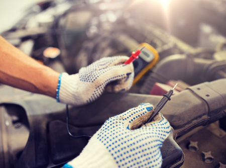 Concepto de servicio, reparación, mantenimiento y personas de automóviles - hombre mecánico de automóviles con batería de prueba de multímetro digital en el taller