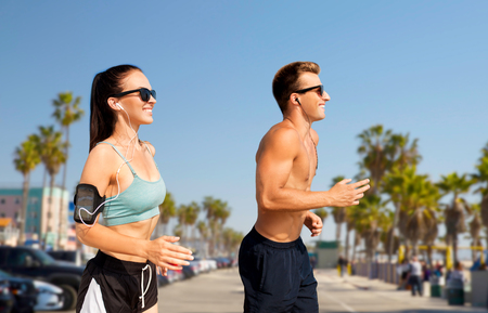 fitness, sport and technology concept - happy couple with earphones and arm bands running over venice beach background in california Stock Photo