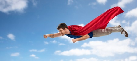super power and people concept - happy young man in red superhero cape flying in air over blue sky and clouds background