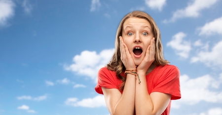 emotion, expression and people concept - shocked or scared teenage girl with open mouth in red t-shirt over blue sky and clouds background