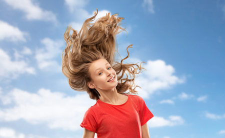 people concept - smiling teenage girl in red t-shirt with long hair waving over blue sky and clouds background