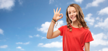 gesture and people concept - smiling teenage girl with long hair in red t-shirt showing ok hand sign over blue sky and clouds background