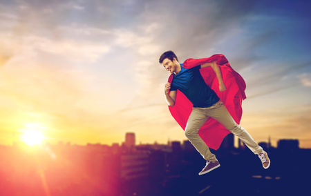 super power and people concept - happy young man in red superhero cape flying in air over sunset in city background