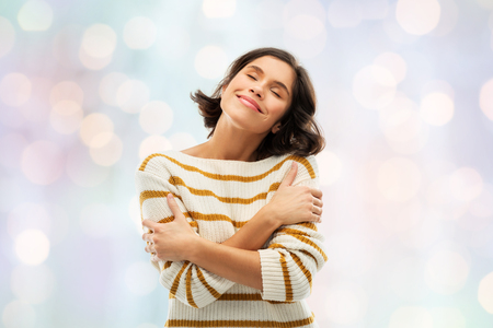 people concept - happy pleased young woman in striped pullover with closed eyes hugging herself over festive lights background