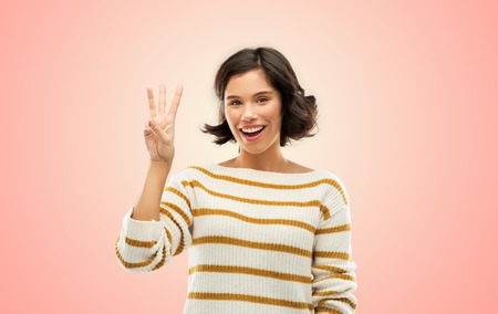 counting and people concept - happy smiling young woman in striped pullover showing three fingers over living coral background Stok Fotoğraf
