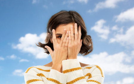 people concept - young woman in striped pullover closing face with hands and looking by one eye through her fingers over blue sky and clouds background
