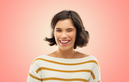 expression and people concept - happy smiling young woman in striped pullover winking over living coral background 스톡 콘텐츠