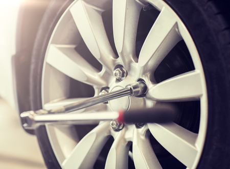 car service, repair and maintenance concept - screwdriver and wheel tire