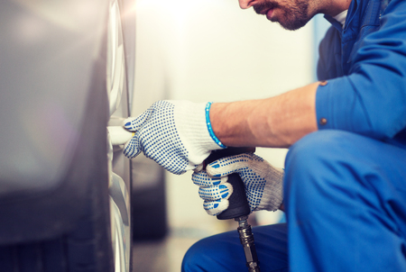 car service, repair, maintenance and people concept - auto mechanic man with screwdriver changing tire at workshop Stok Fotoğraf