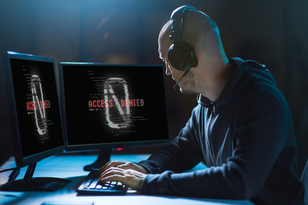 cybercrime, hacking and technology concept - male hacker in headset with access denied messages on computers screens wiretapping or using computer virus program for cyber attack in dark room