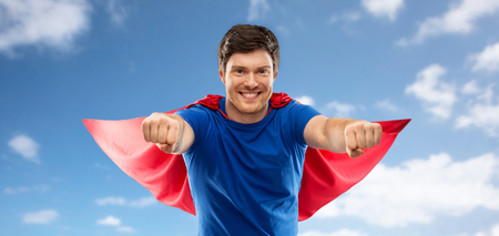 super power and people concept - happy young man in red superhero cape over over blue sky and clouds background Stock fotó