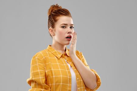 感情、表現と人々の概念 - 灰色の背景の上に手で口を覆う市松模様のシャツで赤い髪の十代の少女