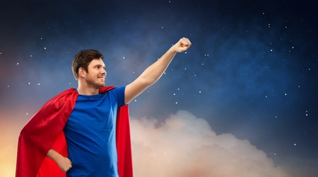 super power and people concept - happy young man in red superhero cape over starry night sky background 版權商用圖片