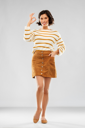 people concept - happy smiling young woman in striped pullover, short skirt and ballet flat shoes showing ok gesture over grey background
